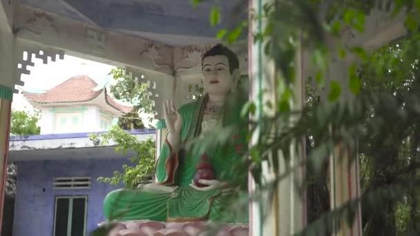 Socha sedícího Buddhy v zelených šatech v buddhistická pagoda. Socha Buddhy v starověkého chrámu. Asijská náboženství a kultura