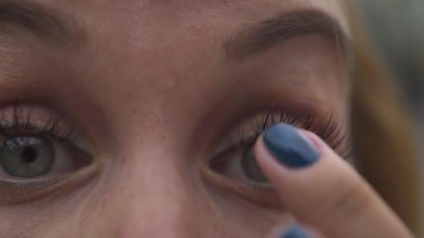 Mladá žena dotýká řas přední kamera zblízka. Ženská tvář, oči, obočí a řasy.