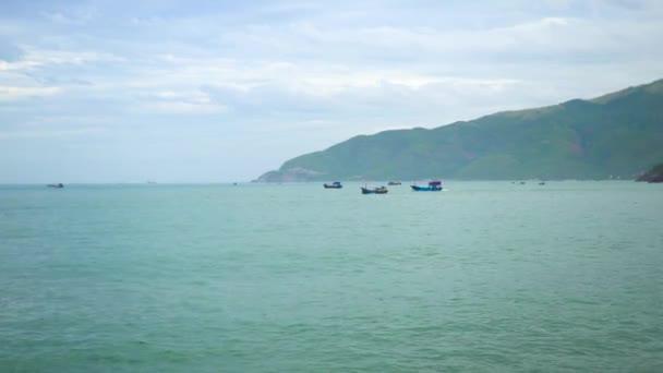 Rybářské lodě plující v moři na zeleném hornatém pozadí. Plachetnice v modrém oceánu. Krásné tyrkysové moře a horské krajiny