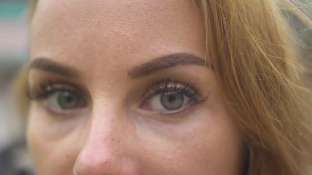 Zárja be a nő arcát és a szeme néz a kamerába. Arc fiatal nő szürke szeme és természetes smink.