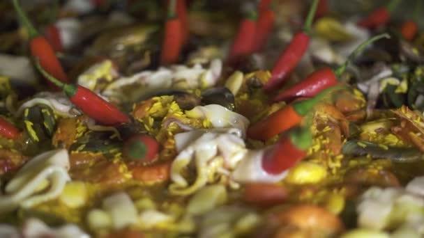 traditionelle spanische Paella mit Muscheln, Garnelen, Tintenfischen und Gemüse in der Pfanne. Nahaufnahme. Kochen spanischer Paella mit roter Paprika und frischen Meeresfrüchten in der Pfanne aus nächster Nähe.