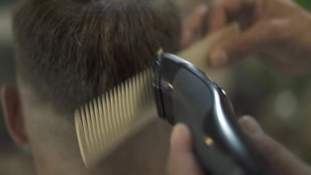 Hairdresser doing hair cut with hair machine and comb in barber shop. Hairdresser making hairstyle with electrical shaver in male salon. Close up hairdressing with trimmer and hairbrush.