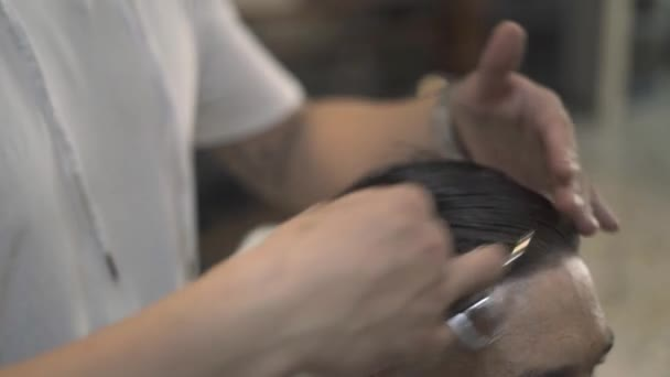 Barber combing wet male hair with comb in hairdressing salon. Hairstylist doing male hairdo in barbershop. Man hairstyle and hair care concept.