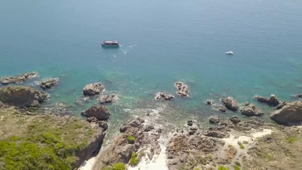 Anténa zastřelil modré moře s plující lodi a horské útesu na pobřeží Jaderského moře. Krásná krajina lodí plujících v tyrkysové moře vody v blízkosti skalnatého útesu. Letecký pohled na křišťálově čisté moře
