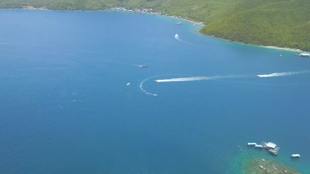 Ship sailing and parasailing in sea bay on green island landscape. Sailing boat and paragliding in blue sea lagoon. Beautiful ocean view from flying drone.