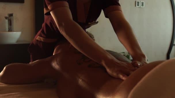 Koncept masáž těla. Žena přijímající olejová masáž v salonu spa. Mladá žena relaxaci ve wellness centru. Těla Relaxace a péče o pleť