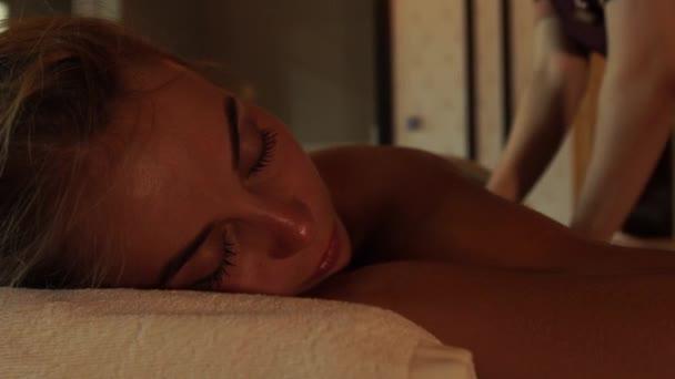 Tvář mladá žena dostává masáž těla v luxusních wellness salonu. Dívka, příjem masáž v kosmetické a lázeňské centrum. Těla Relaxace a péče o pleť.