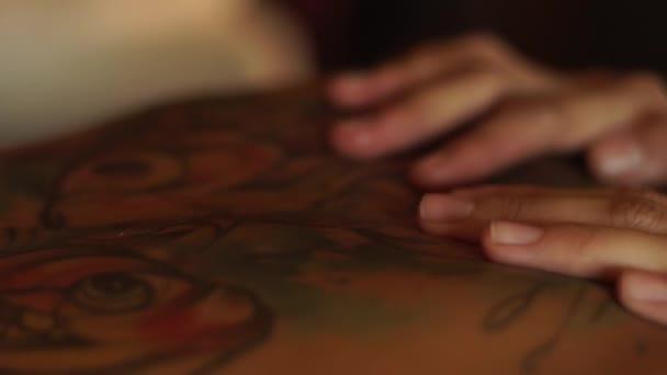 Ruce masseurdoing těla masáž v lázeňském centru. Olejová masáž těla s tetováním. Tělo lázeňské péče a koncepce