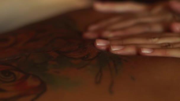 Közelről masszőr csinál test masszázs olaj a spa szalon. Masszázs és spa care koncepciót. Női bőr wit tetoválás.