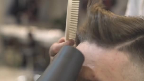 Barber using hair dryer and comb for male hairstyle in salon. Man hair drying in barber shop. Hairstylist drying hipster hair in male salon. Fashion man hairdo concept.