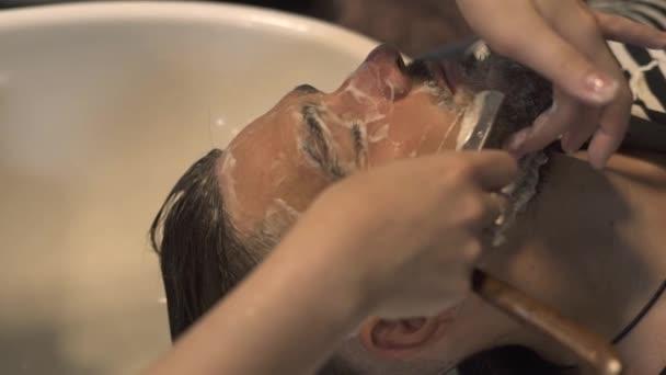 Close up male beard cut with straight razor shave in barber shop. Shaving beard in male salon. Male beard style. Barber shaving hipster man face.