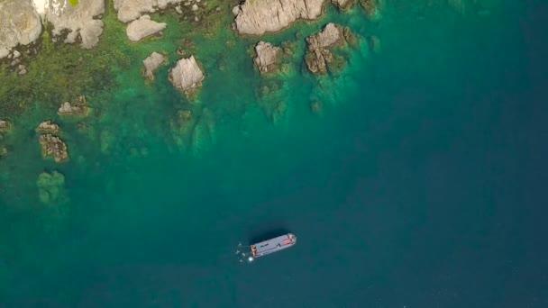 Letecký pohled na plachetnice v modrém moři a horské krajiny útesu. Moře krajina shůry létající dron. Loď v průhledný oceán vody a skalnatého útesu pohled shora