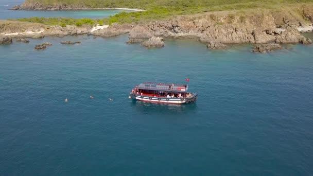 Letecký pohled na plující lodi v modré moře a horu útesu na pobřeží. Turistické lidí, koupání v čisté moře vody a lodní plachta dron zobrazení. Krásné moře zálivu