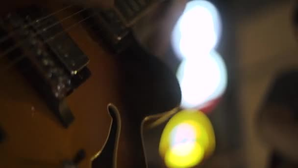 Hudebník hraje hudbu na kytaru struny na koncertě. Detailní záběr kytara player přehrává melodii kytara na koncertních pódiích. Hudební vystoupení na strunné nástroje