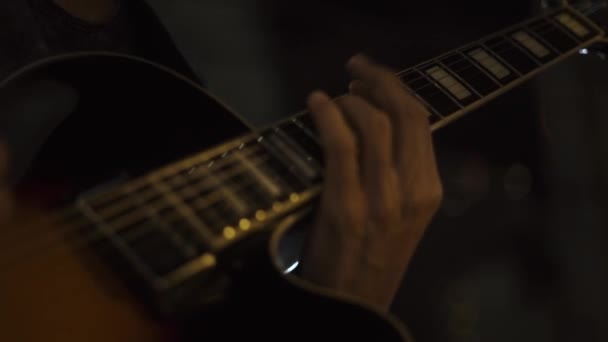 Kytarista hraje rockovou hudbu na koncertních pódiích. Detailní záběr rukou hudebník hraje hudbu na akustickou kytaru. Kytarista hraje melodii na struny