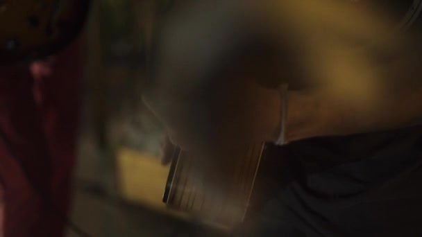 Musician plays music to guitar on performance. Hands of male musician playing melody at acoustic guitar close up. Guitarist playing music on concert.