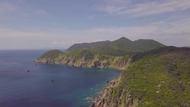 Letecký pohled na lodě plující v modrém moři a zelené horské krajiny. DRONY pohled plachetních lodí v moři a skalnatého útesu na obzoru
