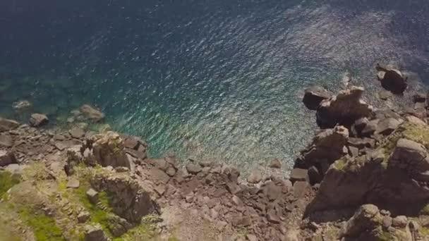 Skalnatého útesu na pobřeží a modrá hukot moře. Pohled shora útesu hory a tyrkysové moře vody. Krajina z létající dron skalnaté pobřeží