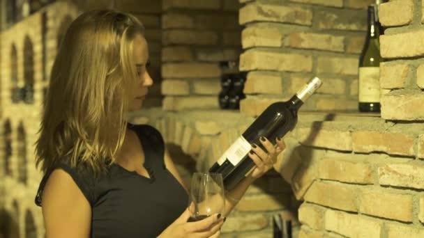 Žena vinař vonící sklenice červeného vína a držel v ruce láhev ve sklepě. Mladá žena, ochutnávek a červené víno ze skla