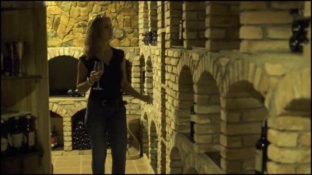 Mladá žena s sklenka na červené víno láhev při pohledu do sklepa. Žena vinař červeného vína v tradiční sklep.