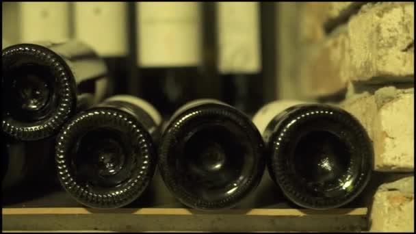 Vinné láhve ležící v zásobníku na sklep zblízka. Skleněné láhve červené a bílé víno, uložené v kamenném sklepě