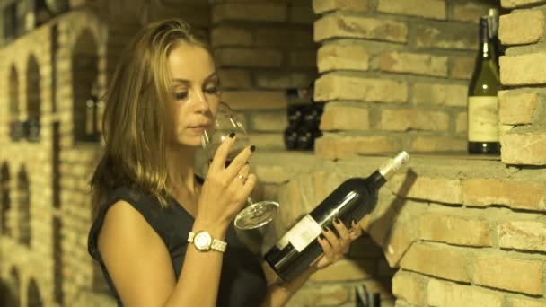 Young woman drinking red wine from glass and looking bottle in cellar. Woman winemaker tasting and drinking red wine from glass in traditional cellar.