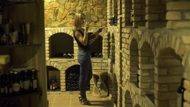 Žena, pití červeného vína ze skla a držel v ruce láhev ve sklepě. Žena vinař ochutnávka červené víno ze skla v tradiční sklep