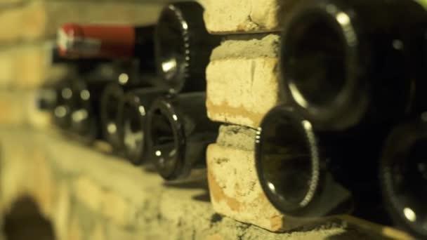 Vinné láhve ležící v zásobníku ve sklepě. Skleněné láhve vína uložená v kamenném sklepě v hospodě