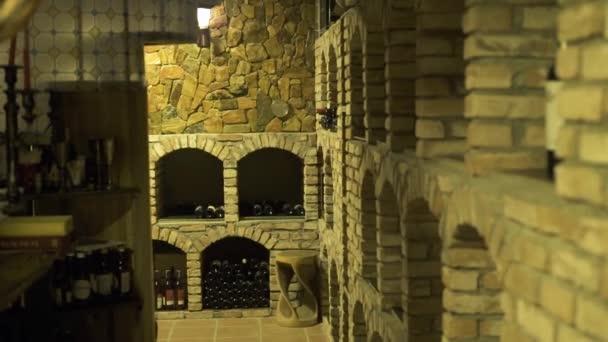 Vinný sklep a skleněné láhve ležící v zásobníku v továrně zblízka. Skleněné láhve červené a bílé víno, uložené v kamenném sklepě