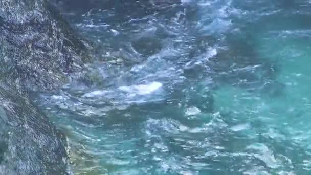 Čistou mořskou vodou stříkající skalnatý ostrov. Modré moře vlny na hoře útes. Tyrkysové vody v oceánu a skalnatého útesu, pěnové a šplouchání pozadí