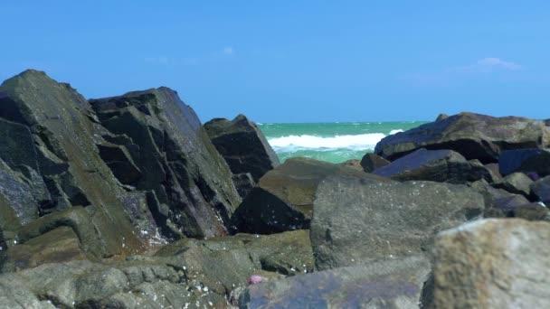 Skalnaté pobřeží a stříkající mořské vody na modré obloze krajiny. Mořské vlny drcení na kamenité pláži. Vodní vlny narážely na kamenité pobřeží v oceánu na pozadí modré oblohy