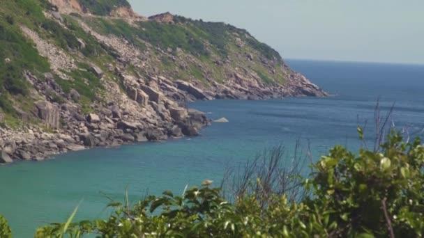 Skalnatého útesu na ostrově a modrou vodou krajinu. Zelené moře ostrov skalnaté pobřeží a modrou vodou na jasné Panorama