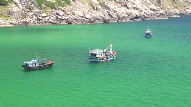 Plachetnice v modrém moři na skalnaté horské krajiny. Rybářské lodě plující v tyrkysové moře vody a skalnatého útesu na ostrově pozadí