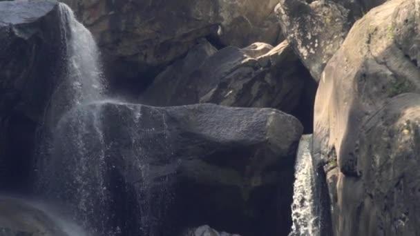 Horský vodopád v deštném pralese. Proud vody vodopád teče po kamenech v horském lese. Tok vody na skalnatém útesu