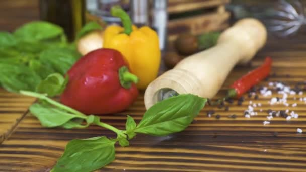 Peperoni rossi e gialli, basilico, pomodori e olio doliva per cucinare cibo Mediterraneo. Verdure fresche, erbe aromatiche e condimenti per il cibo sano preparazione sulla tavola di legno