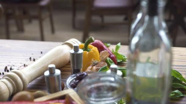 Čerstvý pepř, rajčata, česnek, sůl, pepř, olivový olej a balzamikový ocet salát. Čerstvá zelenina a koření pro přípravu pokrmů na dřevěný stůl v kuchyni restaurace