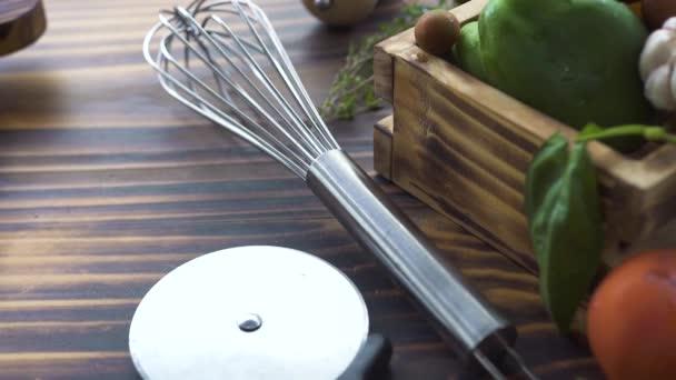 Corolla di cucina, pizza lama, erbe, pepe delle verdure, pomodoro, cipolla, aglio, sale, olive per cucinare il cibo sulla tavola. Chiuda in su verdure e condimenti per la preparazione del cibo sulla tavola di legno