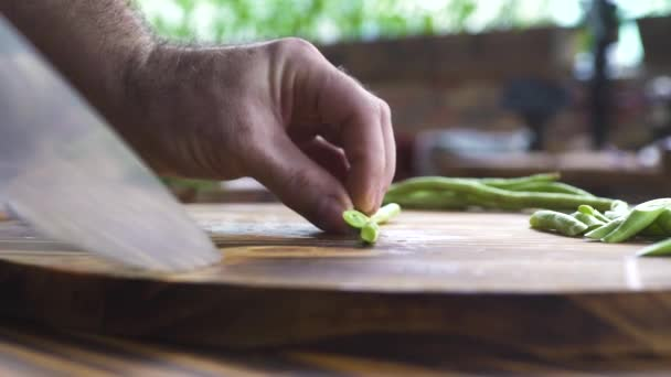 Knife slicing green beans on board close up. Slow motion chef cook cutting green beans on kitchen. Vegetable ingredients for mediterranean cuisine. Vegetarian diet, fitness menu and healthy food.