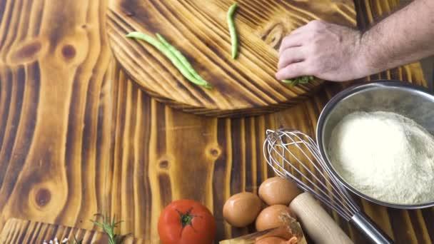 Mani maschii fagiolini di taglio con coltello. Cuoco di carrellata affettare fagioli verdi sulla tavola di legno. Vista superiore taglio verdure ingredienti per il cibo italiano. Cibo cucina per dieta sana