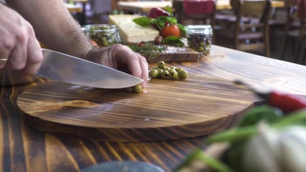 Chef cook chopping green olives with knife on wooden table. Male hands slicing olives for mediterranean salad. Vegatable ingredient for vegetarian cuisine. Cooking food in italian restaurant.