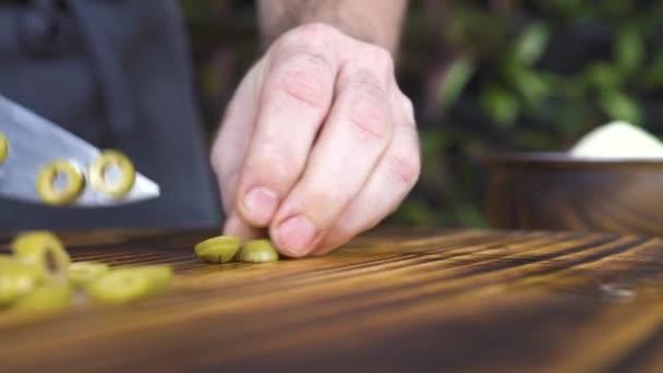 Detail řezu zelené olivy s nožem na dřevěné desce. Šéfkuchař vaří řezů olivy na kuchyňský stůl zpomalené. Proces řezání přísady pro vaření potravin. Zeleninová dieta a zdravé jídlo koncept