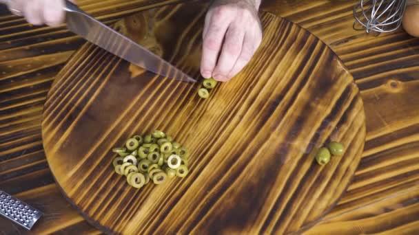 Pohled shora řezání zelené olivy pro Řecký salát na dřevěný stůl. Proces řezání olivy pro vegetariánskou kuchyni. Středomořské přísada na pizzu. Zdravé potraviny a dietní strava. Vaření potravin zblízka