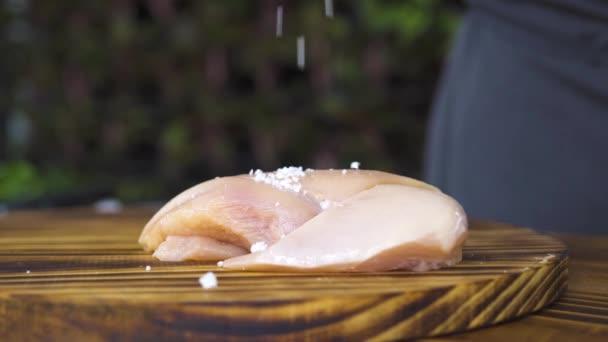 Maso syrové čerstvé kuřecí filet na dřevěný stůl zblízka. Sůl na kuřecí prsa ležící na kuchyňské desce. Proces přípravy zdravé jídlo. Fitness potravin a proteinové diety. Maso nádoby na vaření