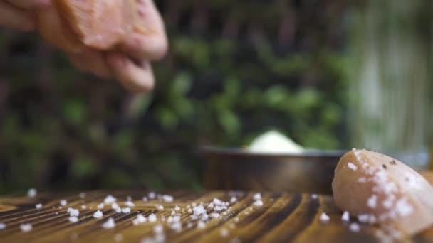 Шеф-повар готовить, поставив сырого куриного филе на деревянный.