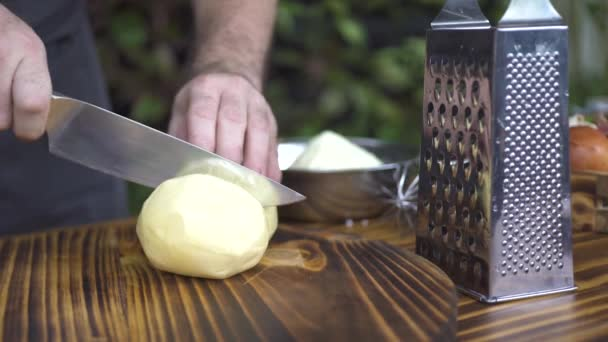 Chef cook cutting with knife cheese on wooden table. Cutting fresh cheese for food preparation. Ingredients for mediterranean, italian, greek cuisine. Process cooking healthy food for fitness diet.