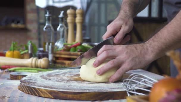 Kuchař kuchař řezání těsta s nožem na pečení dortu zblízka. Baker, krájení těsta pro válcování na dřevěný stůl. Proces přípravy domácí pečivo. Vaření, pekařské výrobky, těstoviny, pizza, občerstvení koncepce