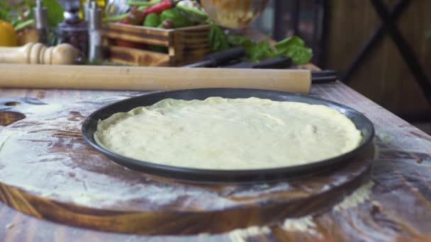 Pizza výrobce připravující pizzu s rajčatovou omáčkou v italské restauraci. Profesionální pizzaillo vaření tradiční pizzu v pizzerii. Proces vaření italské jídlo, koncept národní kuchyně