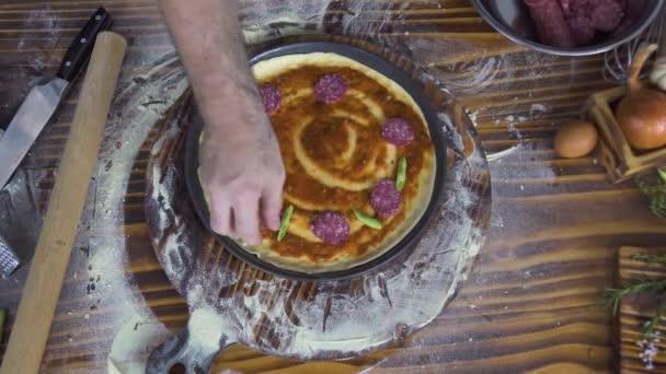 Pizzaillo vaření pizza s klobásou feferonkami na dřevěný stůl pohled shora. Italský šéfkuchař vaří dělat pizzu v pizzerii kuchyni. Proces přípravy tradiční italská jídla. Jídlo připravit koncept