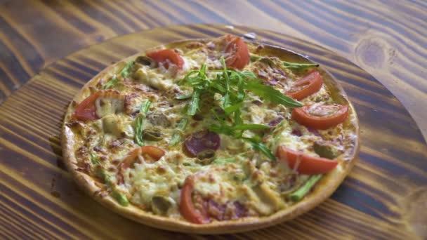 Horká pizza s čerstvými bylinkami na dřevěný stůl. Originální italská pizza s rajčaty, klobásy paprikové a rukola byliny. tradiční italská kuchyně, jídlo koncept