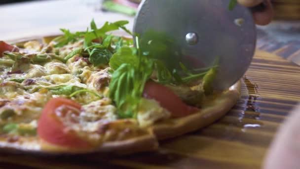 Cook pomocí nože pro řezání pizzu na plátky na dřevěný stůl zblízka. Pizzaillo řezání horké pizza s válečkem nůž v italianpizzeria. Proces přípravy italské jídlo. Jídlo a občerstvení koncepce